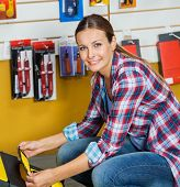 Portrait of smiling mid adult woman analyzing tool case in hardware store
