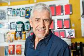 Portrait of confident senior worker smiling in hardware shop
