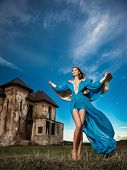 Fashionable beautiful young woman in long blue dress posing with old castle and cloudy dramatic sky