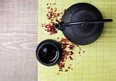 Black teapot, bowl and tea on wooden background