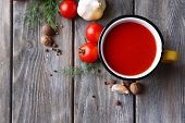 Homemade tomato juice in color mug, spices and fresh tomatoes on wooden background