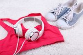 Sport clothes, shoes and headphones on white carpet background.