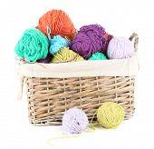 Multicoloured knitting yarn in basket isolated on white