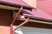 stock photo of gutter  - House red tiled roof with rain gutters and drainpipes - JPG