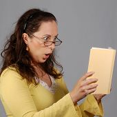Shocked Woman Is Looking At A Book