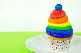 foto of gumballs  - Colorful rainbow swirl cupcake with gumball on white plate - JPG