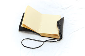 image of leather-bound  - An old fashioned leather bound blank journal open to blank pages shot on white fabric - JPG