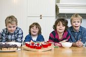 four children smiling in front of freshly baked cupcakes and pies during a baking workshop in a home kitchen
