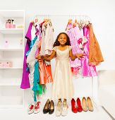 Small beautiful African girl choosing clothes