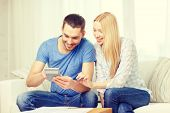 tax, finances, family, home and happiness concept - smiling couple with papers and calculator at home