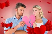 Couple holding two halves of broken heart against red vignette