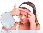 stock photo of pimples  - Girl squeezing her pimples looking in the mirror - JPG