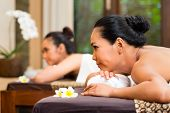 Two Indonesian Asian women in wellness beauty spa having aroma therapy massage with essential oil, looking relaxed