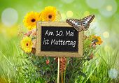 An image of a little chalkboard in the garden with the text 10th of May is Mothers day in german language