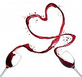 Glasses of red wine splashing out heart shape, isolated on white background