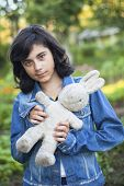 Young dark-haired girl in a denim jacket with an old toy in the hands, outdoors.