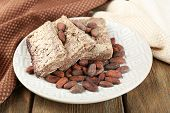 Sunflower halva with cocoa on plate, on wooden background