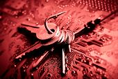 stock photo of hook  - a fish hook with keys on computer circuit board representing phishing - JPG