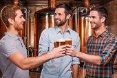 stock photo of containers  - Three cheerful young men in casual wear toasting with beer and smiling while standing in brewery in front of metal containers - JPG