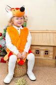 Little Child Girl Dressed In Fox Suit Near Christmas Tree. The Concept Of New Year And Holiday