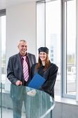 Pretty female university graduate with her happy and proud father, moments after getting the diploma
