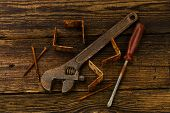 picture of braces  - corner braces screws screwdriver and adjustable wrench on wooden background - JPG
