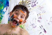 stock photo of finger-painting  - Excited happy little boy doing finger painting standing laughing at the camera with a wide open mouth in front of his artwork with vibrant colors and hand prints - JPG
