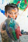 stock photo of finger-painting  - Artistic little boy holding out his paint covered hand to the camera as he stands in front of his modern abstract painting  - JPG
