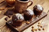 stock photo of chocolate muffin  - Muffins with chocolate and almonds on a wooden table - JPG