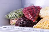 picture of frozen  - Frozen berries and vegetables in bags in freezer close up - JPG