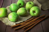 stock photo of sackcloth  - Green apples with cinnamon sticks on wooden table with sackcloth - JPG