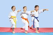 picture of karate kid  - In karategi three athletes are hitting karate kick arm - JPG