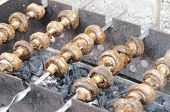 stock photo of brazier  - Brown juicy mushrooms cooked on the brazier - JPG