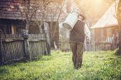 stock photo of kettling  - Senior farmer carrying kettle for milk on his back - JPG