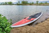 foto of stand up  - red stand up paddleboard on a lake shore in Colorado - JPG