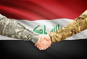 stock photo of iraq  - Soldiers shaking hands with flag on background  - JPG