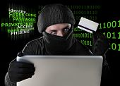 picture of hack  - man in black holding credit card using computer laptop for criminal activity hacking password and private information cracking password too access bank account data in cyber crime concept - JPG