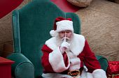 stock photo of shh  - Santa Claus saying shhh toward the camera while sitting in big green chair - JPG