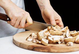 image of crimini mushroom  - Chef cutting the mushrooms on a wooden board - JPG
