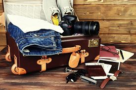 stock photo of packing  - Packed suitcase of vacation items on wooden background - JPG