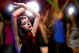 stock photo of debauchery  - intoxicated female dancing at a nightclub and high on drugs or drunk - JPG