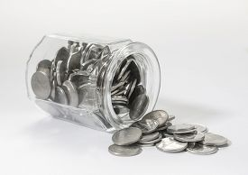 foto of dirhams  - UAE dirham coins spilling out from a glass jar - JPG