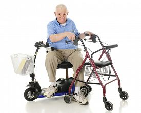stock photo of crippled  - A senior man sitting sideways on his power scooter while holding onto the handles of his wheeling walker - JPG