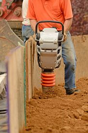 stock photo of vibration plate  - Commercial development building contractor working on building site installing a retaining wall - JPG