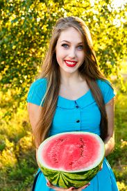 pic of cucurbitaceous  - young attractive girl holding half of ripe watermelon - JPG