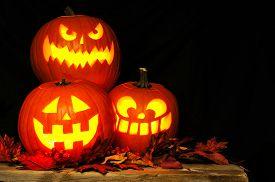 foto of jack o lanterns  - Stacked Halloween Jack o Lanterns illuminated at night with old wood and autumn leaves - JPG