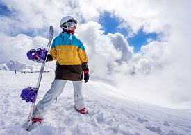 image of snowboarding  - Portrait of woman snowboarder on background beautiful landscape of snowy high mountains of Caucasus at Krasnaya Polyana standing with snowboard - JPG
