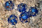 image of x-max  - Clear glass Christmas balls decorated with blue sparkles.