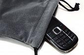 stock photo of handphone  - A still photo taken on a candy bar handphone slipping out of a pouch - JPG