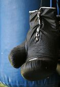 picture of pugilistic  - close up of black boxing glove against blue punching bag - JPG